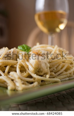 A dish of spaghetti with pesto garlic and chicken with a glass of white wine. Shallow depth of field. - stock photo