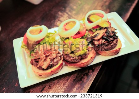 A dish of three mini-burgers, each with different flavor. - stock photo
