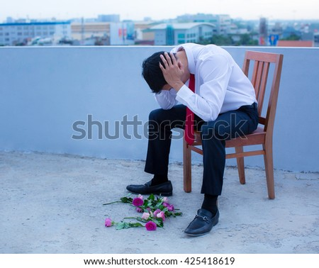 A disheartened man in a suit, broken-hearted after being rejected. - stock photo