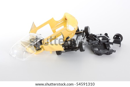 A dismantled toy car, divided in several pieces. - stock photo