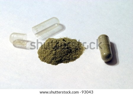 A display of an herbal powder capsule and an opened capsule with the contents in a pile. - stock photo