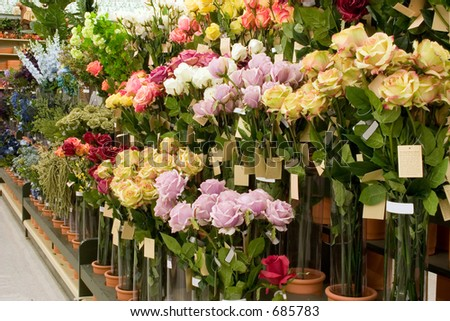 A display of artificial flowers for sale in this store - stock photo