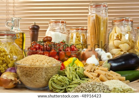 A display of healthy foods including various vegetables, jars of pasta, rice, seeds, onions, garlic, olive oil, aubergine, tomatoes, peppers, spaghetti and courgettes - stock photo