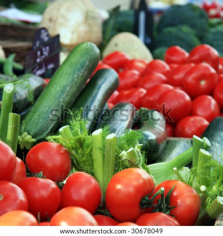 A display of tomatoes, courgettes and fennel for sale at a market - stock photo