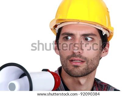 A disturbed tradesman holding a megaphone - stock photo