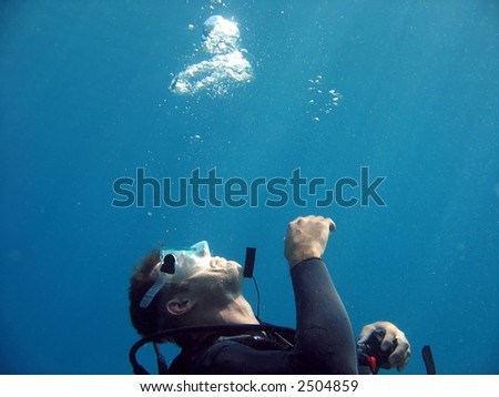 A diver blowing bubbles in the water. - stock photo