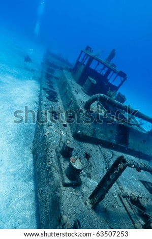 A diver can be seen in the background exploring the underwater wreck.  Shot off of Grand Cayman. - stock photo
