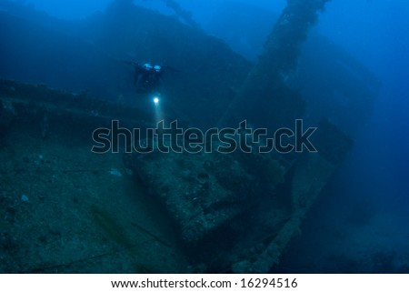 A diver hovering above a Japanese Type 97 light tank, on the deck of the Japanese cargo ship, Nippo Maru. - stock photo