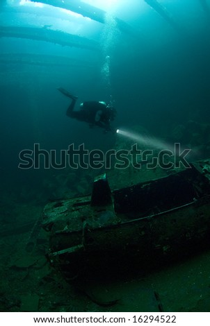 A diver inspecting airplane parts in the hold of the Japanese aircraft transport, Fujikawa Maru. - stock photo