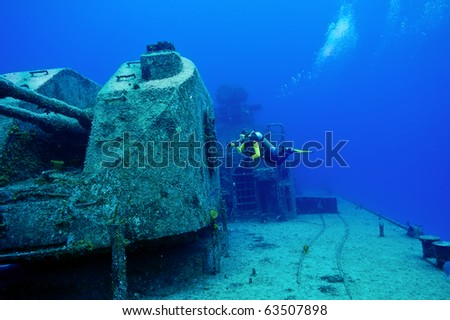 A diver is exploring around the big gun on the wreck of the Capt.Keith Tibbetts, the only Russian warship in the Western Hemisphere that is within recreational diving limits. - stock photo