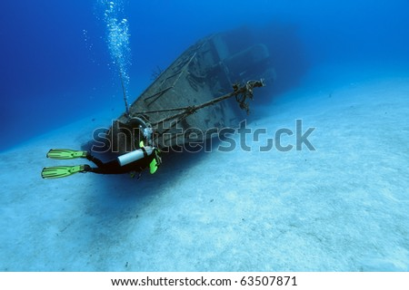 A diver is exploring around the bow of the wreck of the Capt.Keith Tibbetts, the only Russian warship in the Western Hemisphere that is within recreational diving limits. - stock photo