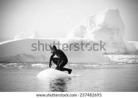 A diver on the ice against the blue iceberg. Antarctica - stock photo
