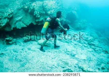 A diver walking underwater, below the hot spring, the different density of hot and cold water makes the vision blurry. Barracuda Lake, Coron, Philippines. - stock photo