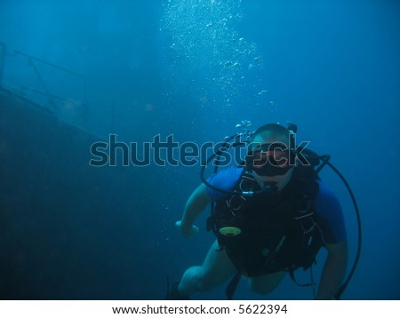 A diver with a wreck in the background - stock photo