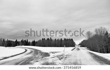 A diverging gravel road with one going straight and one curving to the left in rural black and white winter landscape  - stock photo