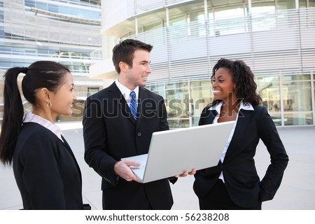 A diverse attractive man and woman business team at office building with laptop computer - stock photo
