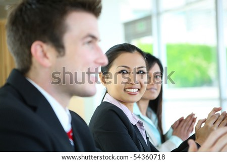 A diverse attractive man and woman business team  clapping at meeting - stock photo