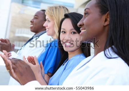A diverse attractive man and woman medical team at hospital building - stock photo