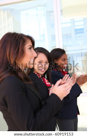 A diverse attractive woman business team at office building clapping - stock photo