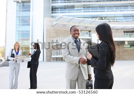 A diverse business man and woman team handshake at office building