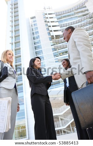 A diverse business man and woman team handshake at office building - stock photo