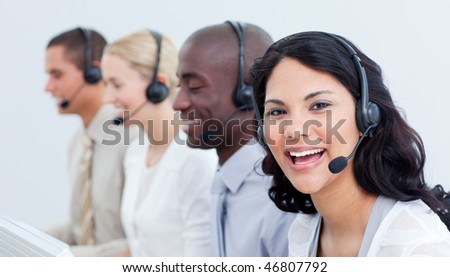 A diverse business team talking on headset in a call center - stock photo