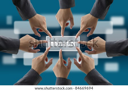 A diverse business team with hands together push Innovation button for brainstorm concept - stock photo