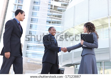 A diverse ethnic business team shaking hands at office building