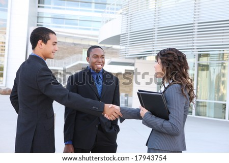 A diverse ethnic business team shaking hands at office building - stock photo