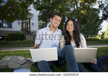 A diverse group of college students working on their laptops on campus