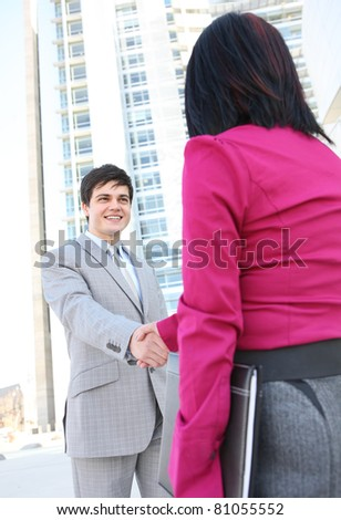 A diverse man and woman  business team shaking hands at office building - stock photo