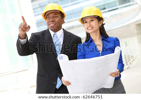 A diverse  woman and man working as architects on a construction site (Focus on Woman)