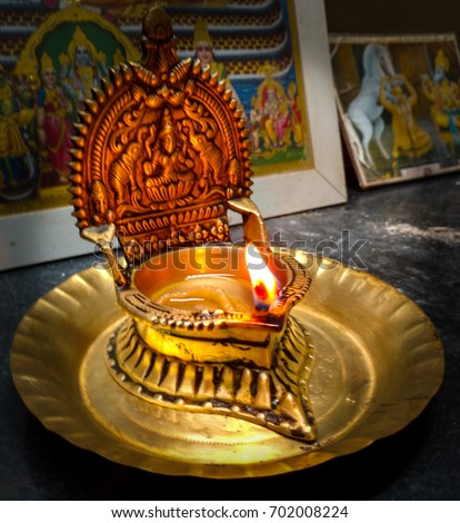 A Diya Or A Holy Lamp, With An Image Of A God, Lit By