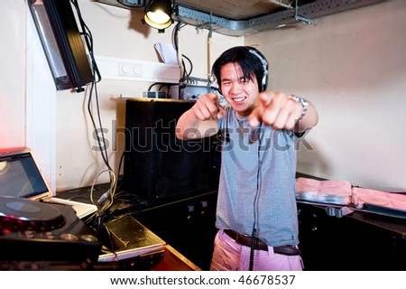 A Dj in a dj booth smiling and pointing at the camera - stock photo