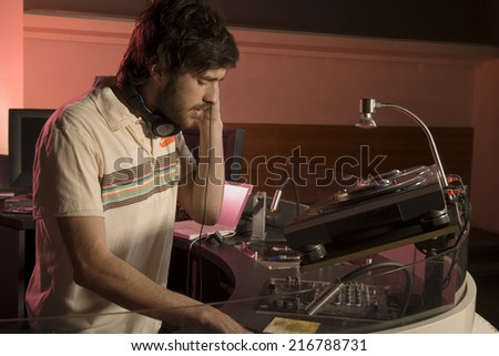 A DJ playing at a nightclub. - stock photo