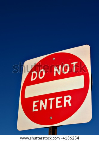 A Do Not Enter road sign against a deep blue sky - stock photo
