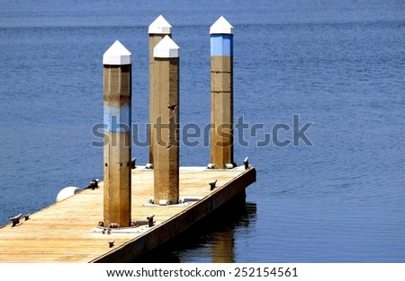 A dock in a harbor for sailboats with poles. - stock photo