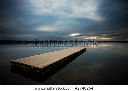 A dock in a lake with the reflection of the sky - stock photo