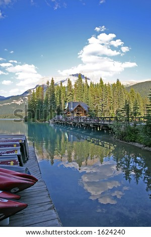 A dock of boats on a tranquil mountain lake with a small cabin in the background. - stock photo