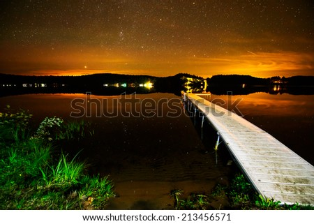 A dock on a lake under a starry sky after sunset.  Image contains some grain due to the high ISO and long exposure required for this type of photography.   - stock photo