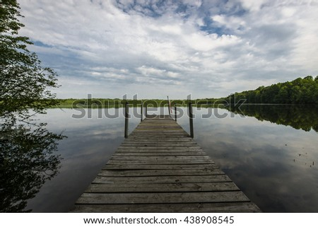 A dock protruding into a pristine lake in central New York. The lake is reflecting the clouds and the blue sky.  - stock photo