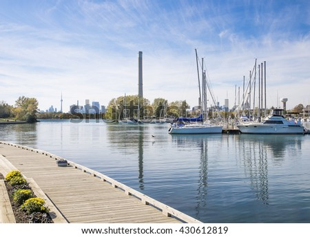 A dock with a lone tackle box overlooks the calm waters of a harbor containing moored pleasure boats. The Toronto Canada downtown skyline in the distance.  - stock photo