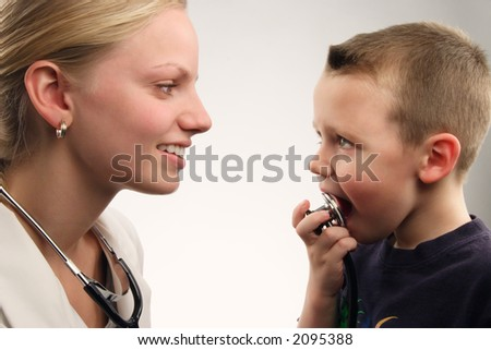 A doctor and her young patient. Gray gradient and landscape format. - stock photo