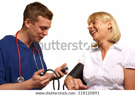 A doctor and patient sharing a joke while checking blood pressure.