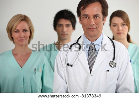 A doctor and three nurses behind him, all looking at us. - stock photo