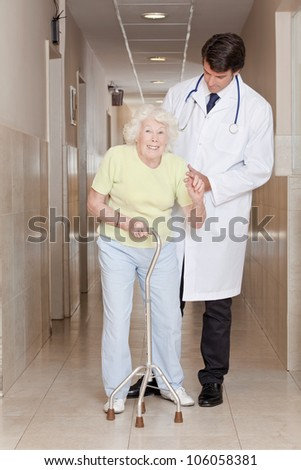 A doctor assisting a senior citizen onto her walking stick. - stock photo