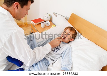 a doctor at home visits. examines a sick child. - stock photo
