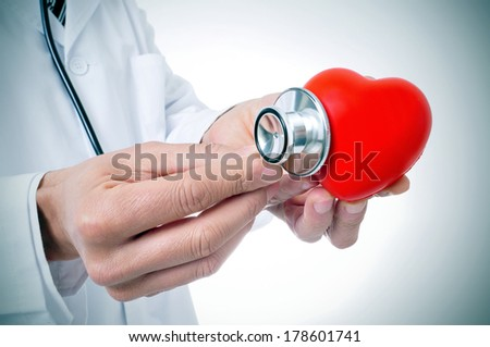 a doctor auscultating a red heart with a stethoscope - stock photo