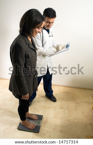 A doctor checks the weight of a patient on a scale. - vertically framed - stock photo