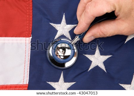 A doctor examines an American flag with a stethoscope.  Image can be used for economic or medical inferences.